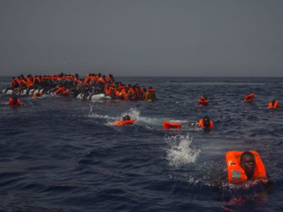 Refugees, having left Libya, flee a sinking boat in the central Mediterranean