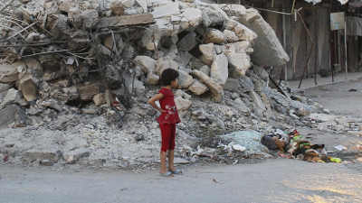Young child in the aftermath of airstrikes in Syria